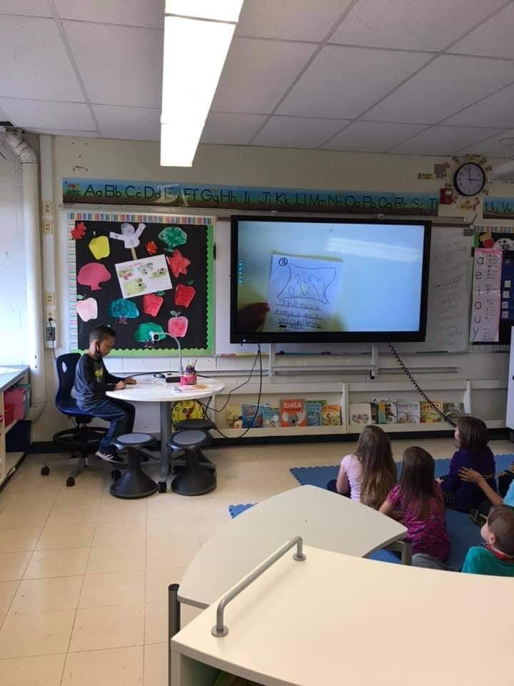 Student sharing his writing through the smart TV as his classmates watch!